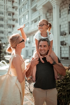 Mãe carinhosa. linda mulher conversando com sua filha sorridente e mostrando como ela é alta, sentada nos ombros de seu pai.