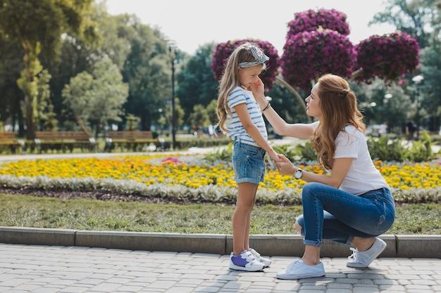 Mãe carinhosa. mãe loira carinhosa acalmando a filha após cair da árvore no parque