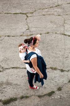 Mãe carrega a menina de volta em estilingue no asfalto urbano, bebê vestindo