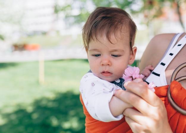Mãe carrega um bebê infantil em estilingue no parque. primavera. conceito de parentalidade natural