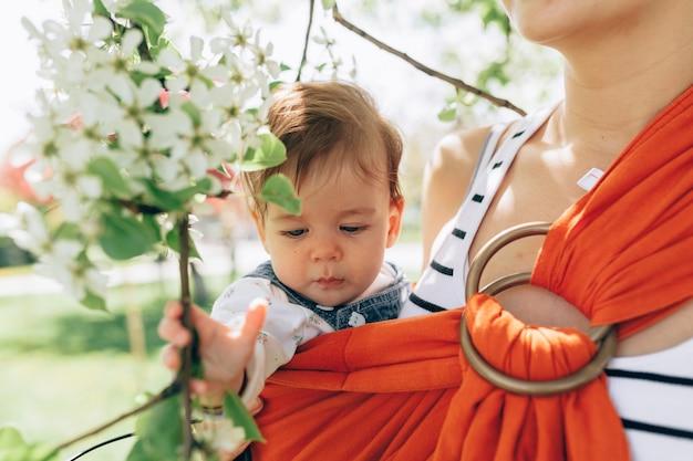 Mãe carrega um bebê infantil em estilingue no parque.
