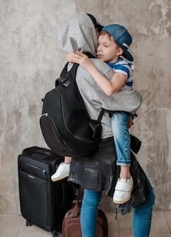 Mãe carrega um filho pequeno em uma mala na sala de espera de transporte.