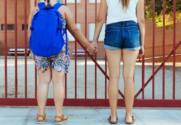 Mãe carregando a filha para a escola. escola em segundo plano.