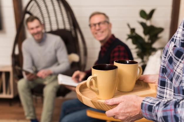 Mãe carregando bandeja de xícaras com desfocado pai e filho