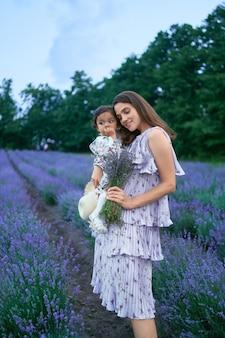 Mãe carregando filha pequena e buquê de lavanda