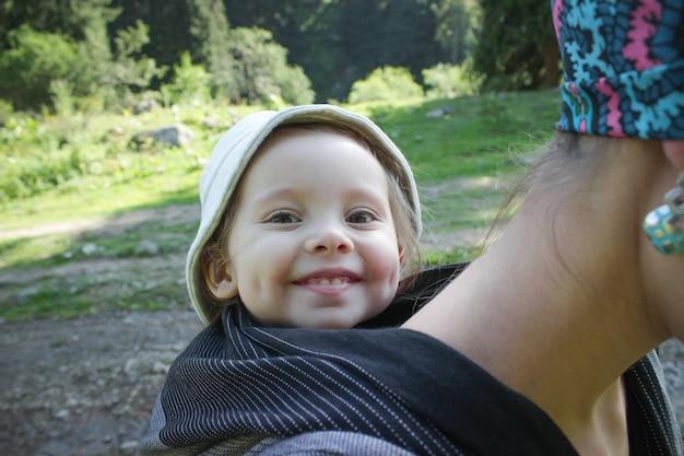 Mãe carregando um bebê sorridente de dois anos em um envoltório de tecido preto. rastreamento, ao ar livre.