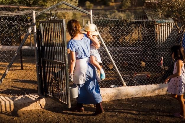 Mãe, carregar, dela, filha, entrar, em, a, aves domésticas, portão