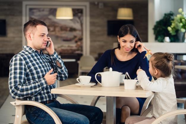 Mãe caucasiana e criança menina no restaurante enquanto o pai ocupado está falando pelo celular.