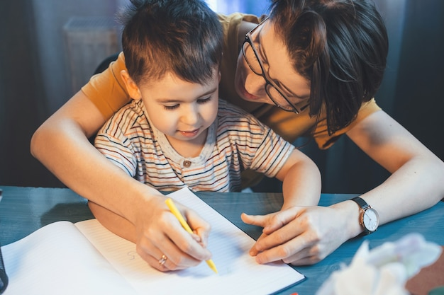 Mãe caucasiana e prestativa está ensinando o filho a escrever segurando a mão dele