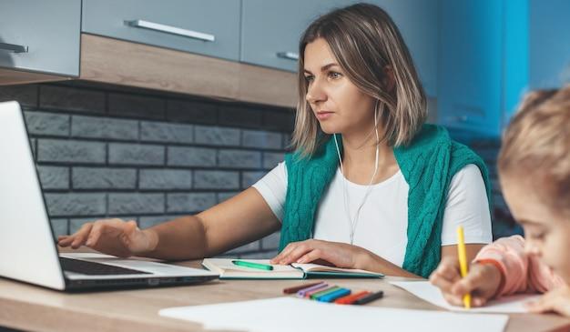 Mãe caucasiana está concentrada em seu trabalho no laptop enquanto a filha está desenhando ela na cozinha
