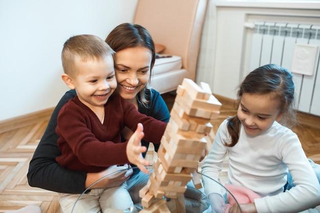 Mãe caucasiana, filho e filha brincando de jenga na mesa de vidro sorrindo juntos