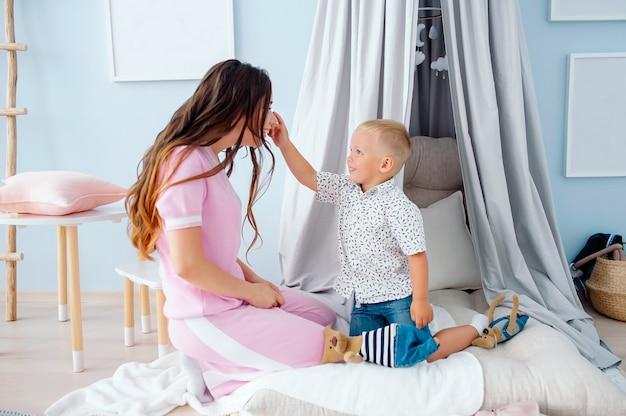 Mãe caucasiana jovem bonita sentada no chão na sala de crianças brincando com filho pequeno feliz em idade pré-escolar sorrindo