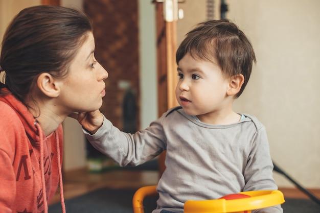 Mãe caucasiana sardenta e filho em um carro de plástico conversando na sala de estar no chão