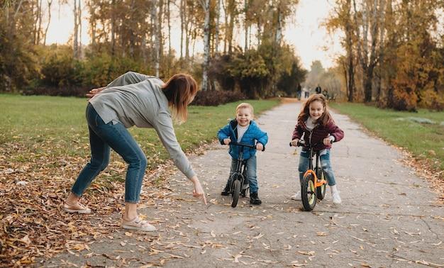 Mãe caucasiana se divertindo com as crianças durante um passeio de bicicleta no parque