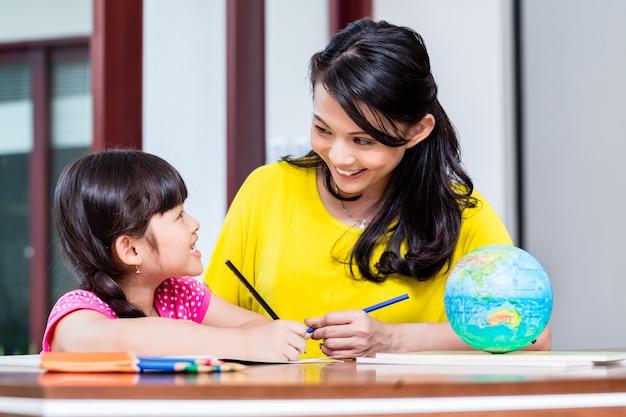 Mãe chinesa fazendo lição de casa de escola com criança