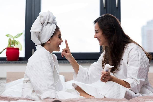 Mãe colocando creme de cuidados com a pele no rosto de filhas