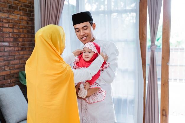 Mãe colocando hijab em seu bebê