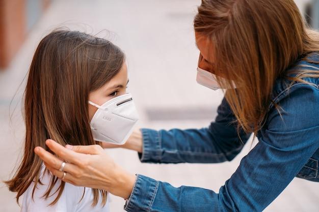 Mãe colocando máscara facial em sua filha na rua