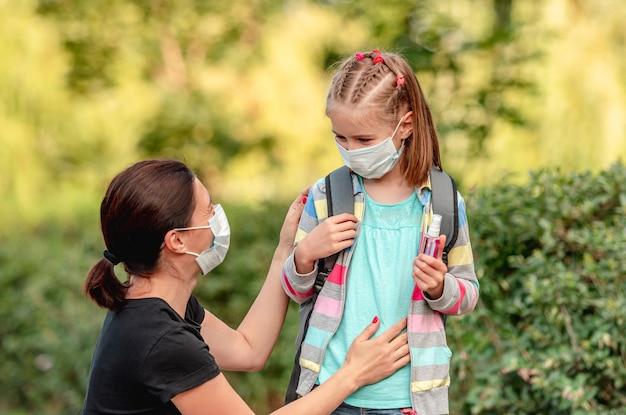 Mãe colocando máscara protetora na filha antes de voltar para a escola