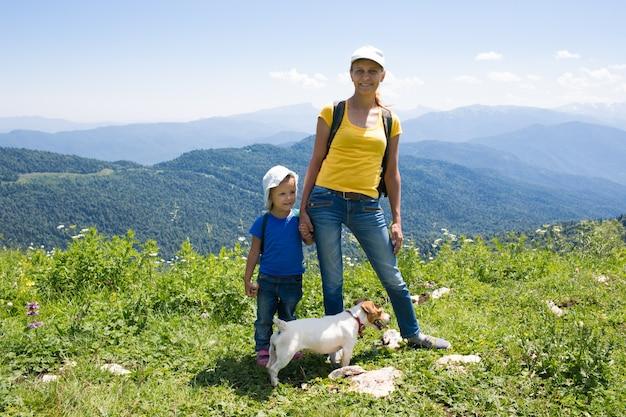 Mãe com a filha de uma menina viajando nas montanhas com um cachorro