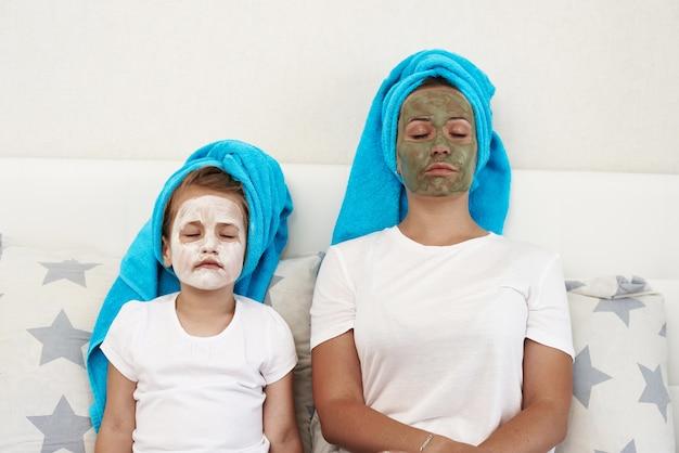 Mãe com a filha dela fazendo máscara facial de argila.
