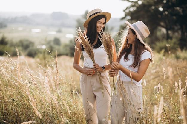 Mãe com a filha junto no campo