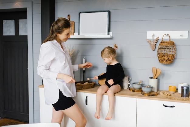 Mãe com a filha na cozinha cozinhando juntas