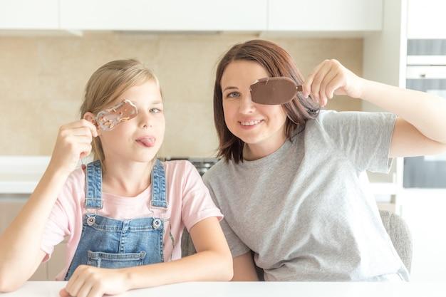 Mãe com a filha na cozinha tomando sorvete, boas relações de pai e filho, conceito de família feliz