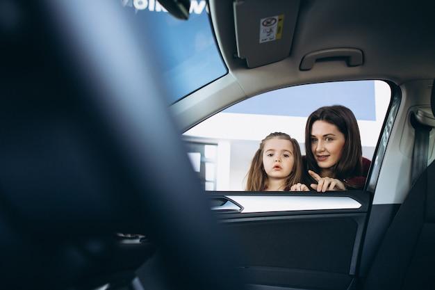 Mãe com a filha olhando para dentro de um carro em uma sala de exposições