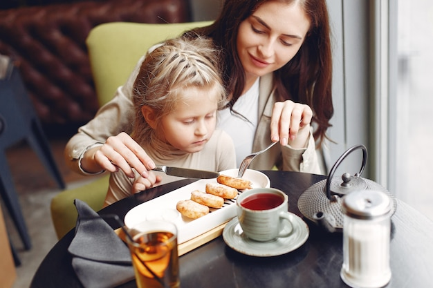 Mãe com a filha sentada em um café