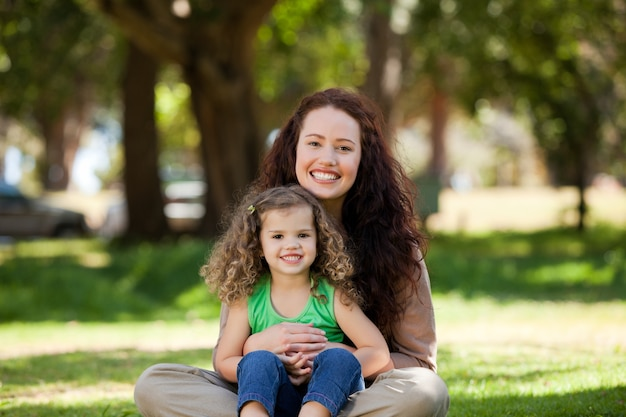 Mãe com a filha sentada no jardim