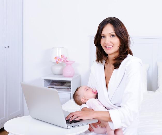 Mãe com bebê e com laptop em casa