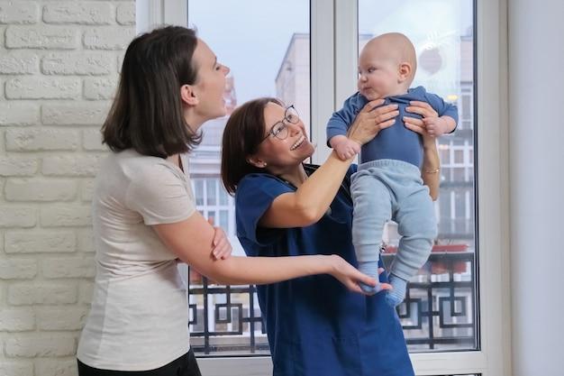 Mãe com bebê filho de sete meses conversando com médico