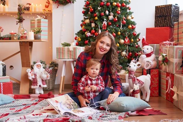 Mãe com bebê na cozinha decorada para o natal.