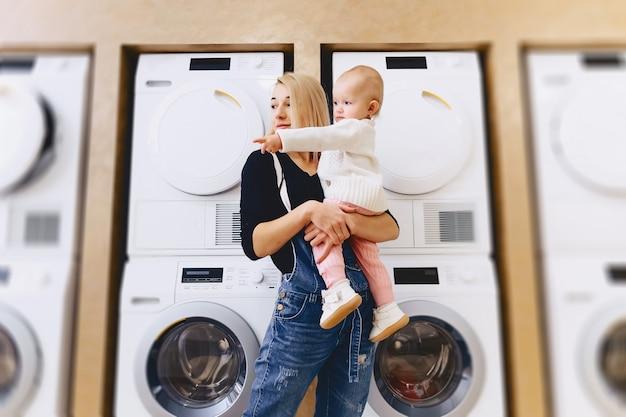 Mãe com bebê no fundo de máquinas de lavar roupa