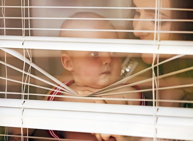 Mãe com bebê olhando através das cortinas