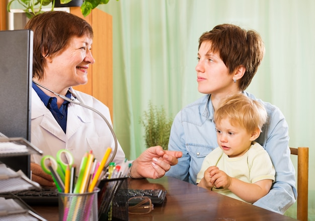 Mãe com bebê ouvindo médico pediatra
