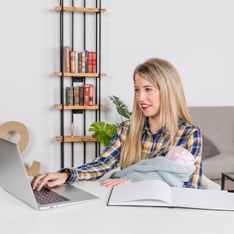 Mãe com bebê trabalhando com laptop em casa