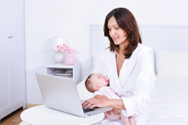 Mãe com bebê usando laptop no quarto