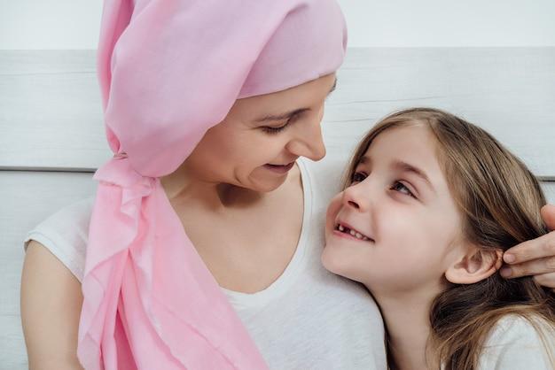 Mãe com câncer, usando um lenço de cabeça rosa, olha com ternura para sua linda filha loira.