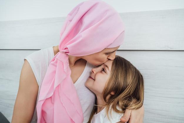 Mãe com câncer, usando um lenço rosa na cabeça, dá um beijo carinhoso em sua linda filha loira.