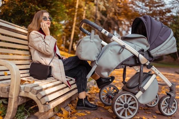 Mãe com carrinho falando ao telefone