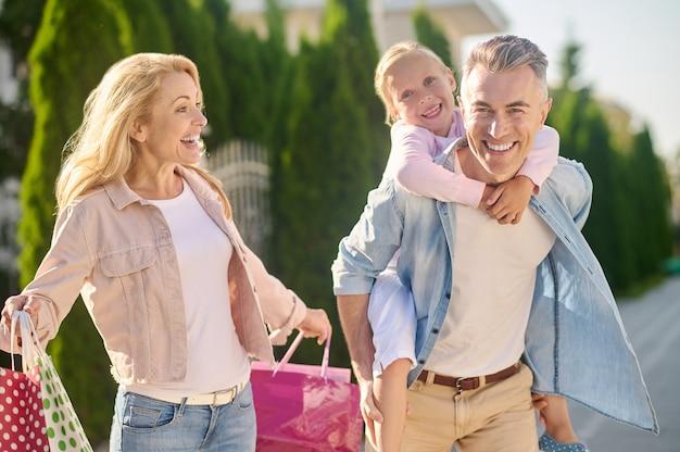 Mãe com compras e pai segurando filha nas costas