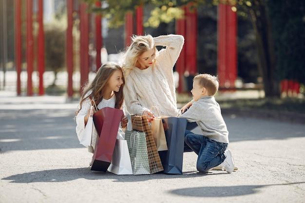 Mãe com criança com sacola de compras em uma cidade