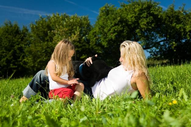 Mãe com criança e cachorro na grama