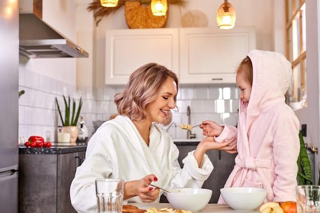 Mãe com criança, menina, comendo saboroso mingau no café da manhã, filha está tratando a mãe de colher, na cozinha clara em casa