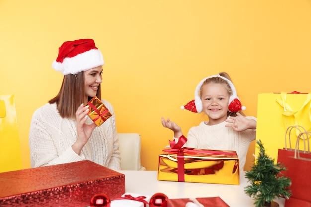 Mãe com criança sentada na mesa com presentes e uma pequena árvore de natal