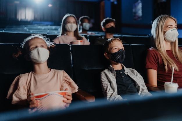 Mãe com crianças pequenas felizes assistindo filme no cinema, o conceito de coronavírus.