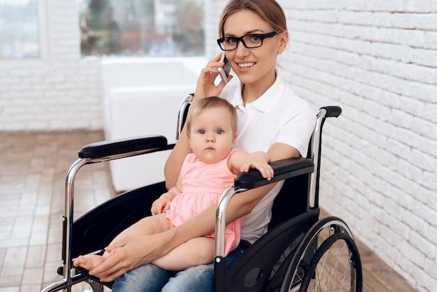 Mãe com deficiência em trabalho de cadeira de rodas com recém-nascido