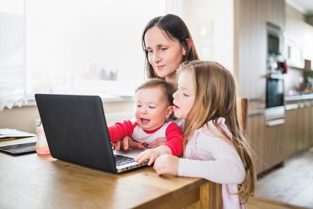 Mãe, com, dela, crianças, olhando portátil